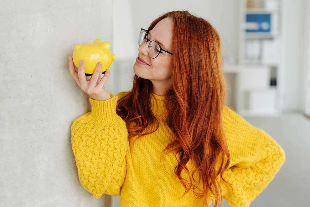 Woman holding a piggy bank looking happuy