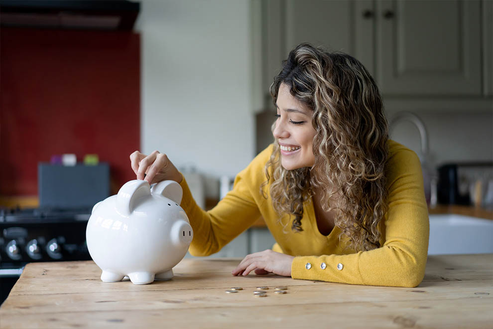 Woman adding coins to piggy bank at kitchen counter