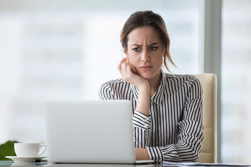 Woman at computer looking worried and annoyed